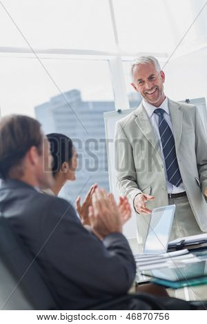 Colleagues applauding the manager during a meeting in the meeting room