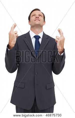 Businessman with fingers crossed is looking up on white background