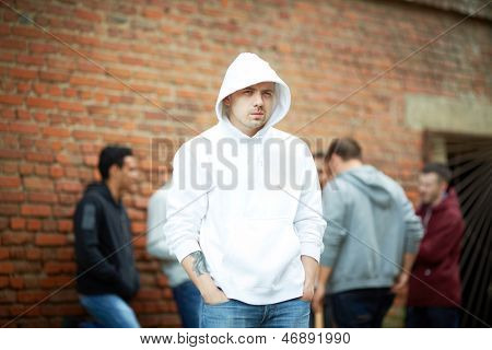 Portrait of angry guy looking at camera with his friends on background