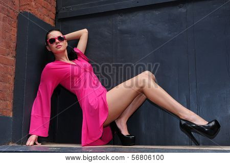 Attractive brunette model posing in pink dress