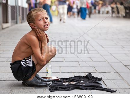SARAJEVO, BOSNIA AND HERZEGOVINA - AUG 11: Sevdalija Osmanovic, 10 years old, sings on street to bypassers on August 11, 2012 in Sarajevo, B&H. He sings in order to provide money for his family.