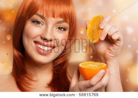 Redhead girl holding orange