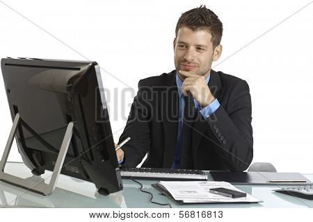 Young businessman working with computer, smiling.