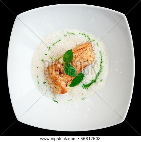 Braised fish fillet with froth sauce shot from above isolated on black