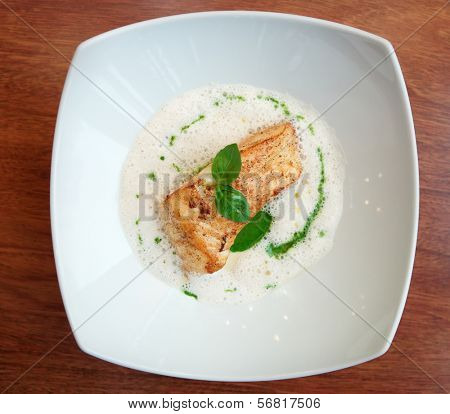Braised fish fillet with froth sauce shot from above