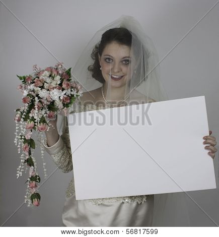 Beautiful young bride holding blank sign