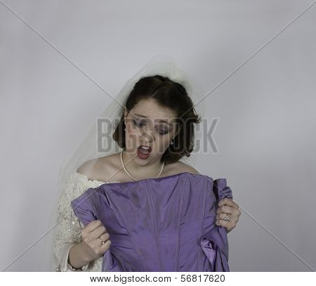 Bride holds up bridesmaid's dress and makes a face