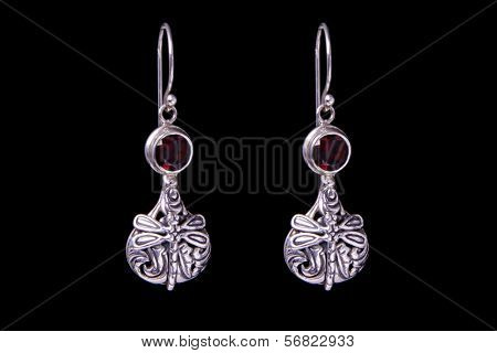 Silver earrings on a black background