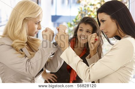 Angry female office workers fighting at workplace, young colleague watching with interest at background.