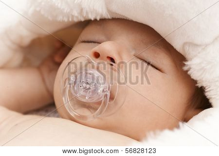 Closeup photo of adorable newborn baby sleeping with dummy.