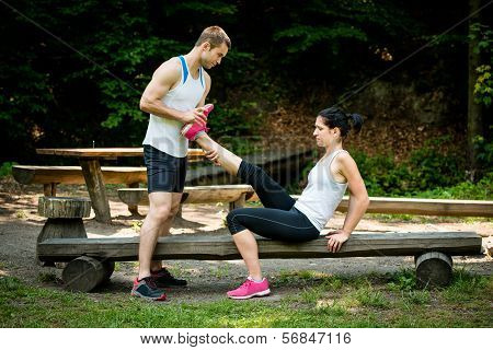 Man stretches womans leg - muscle spasm after sport training poster