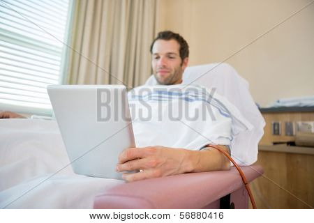 Happy young male patient using tablet computer during renal dialysis treatment in hospital room