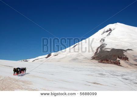 Climbers rising on a snow slope of high peak, a glacier covered with snow