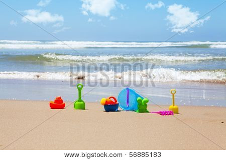 Plastic Beach Toys On Beach With Sea In Background