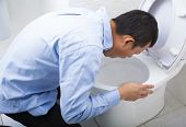 Young man drunk or sick vomiting in toilet at home poster