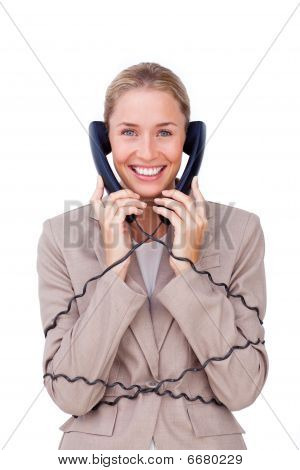 Smiling Businesswoman Tangled Up In Phone Wires