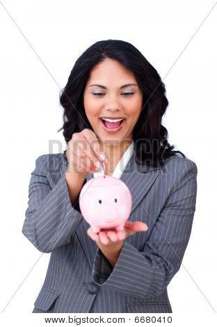 Happy Ethnic Businesswoman Saving Money In A Piggybank
