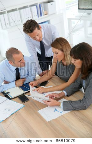 Group of business people meeting around table with tablet