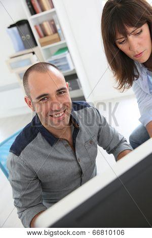 Workmates working on desktop computer