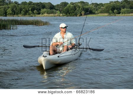 Man Fishing and Paddling in Kayak