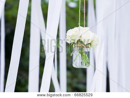 White Roses In A Glass Vase With White Ribbons