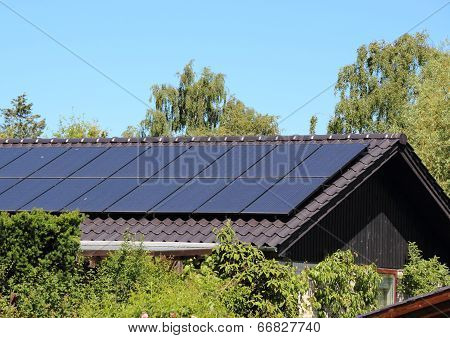 Solar Collector On House Roof With Blue Sky