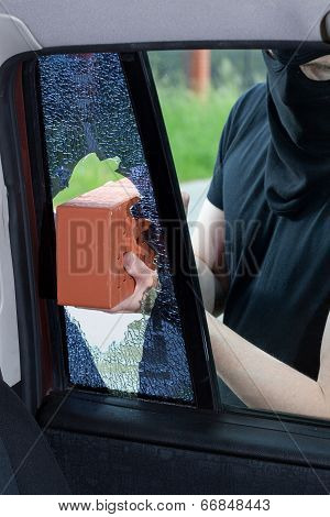 A Burglar Breaks A Window In The Car