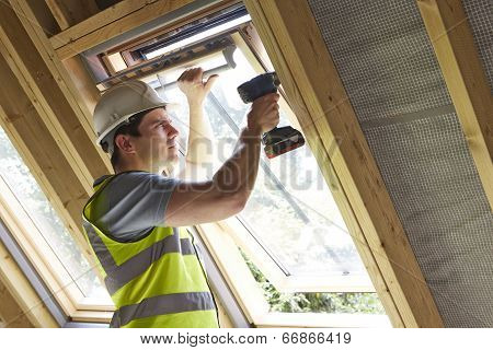 Construction Worker Using Drill To Install Window