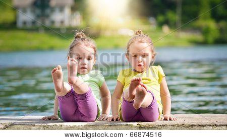 Twing Girls Exercising On A Lake Shore