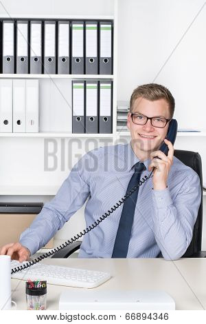 Man Is Phoning At The Desk In The Office