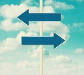 Two blank road signs pointing in opposite directions, blue sky background in vintage style. poster