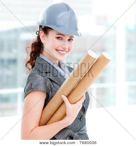 Portrait Of A Smiling Female Architect Holding Blueprints