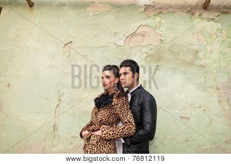 Handsome young fashion man embracing his lover from the back while she is holding both hands in pockets, lookin away.