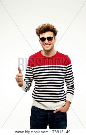 Happpy man in sunglasses with thumb up over gray background