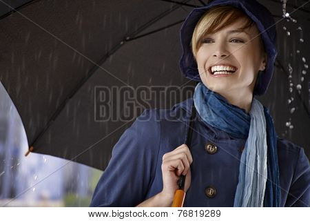 Happy young woman using umbrella in rain, smiling.