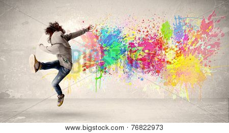 Happy teenager jumping with colorful ink splatter on urban background concept