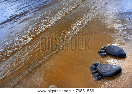 pair of feet made from pebbles on the sea sand  texture surface backdrop