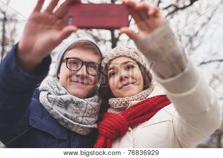 Amorous dates in winterwear taking selfie outdoors