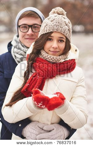 Happy girlfriend in casual winterwear and her boyfriend embracing her behind looking at camera outdoors