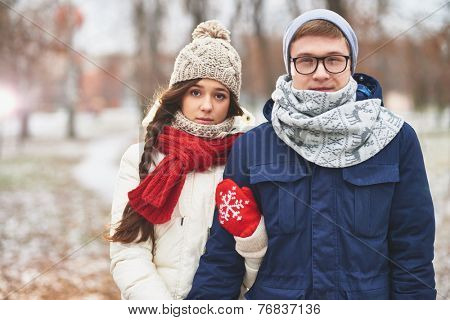 Portrait of cute young dates in stylish winterwear looking at camera outdoors