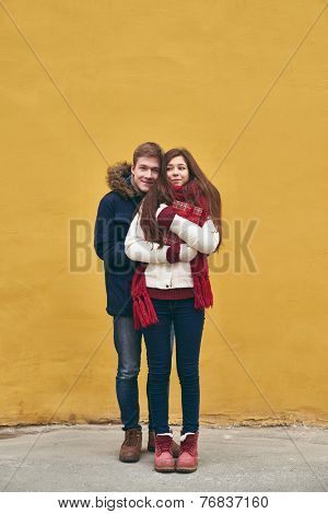 Portrait of young dates in winterwear posing outdoors