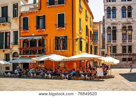 VENICE, ITALY - JULY 7, 2007: Tourists rest and eat in Art blu cafe. The Art Blue Cafe rises in the center of Venice in Campo Santo Stefano just in front of the Conservatory in Venice.