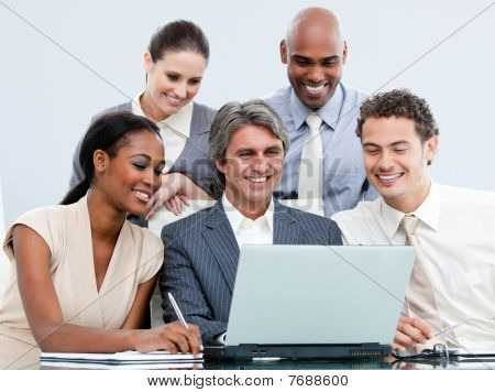 Happy Mixed Businessteam Looking At The Laptop