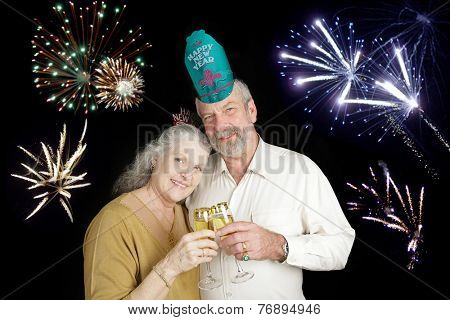 Beautiful senior couple celebrating a Happy New Year with a champagne toast, while fireworks go off in the background.