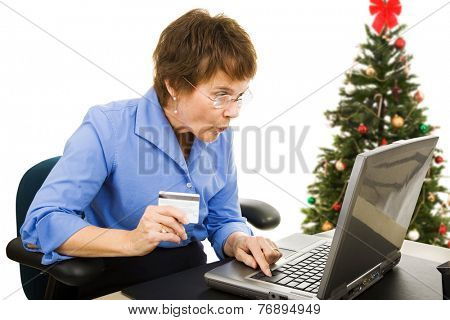 Mature woman finds a bargain shopping online for Christmas presents.  Isolated on white.