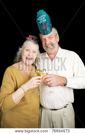 Senior couple a bit drunk on champagne at a New Year's Eve party.  Black background.