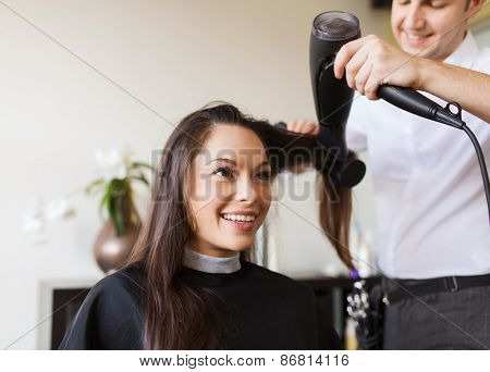 beauty, hairstyle and people concept - happy young woman and hairdresser with fan making hot styling at hair salon poster