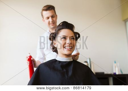 poster of beauty, hairstyle and people concept - happy young woman with hairdresser with hair spray fixating hairdo at salon