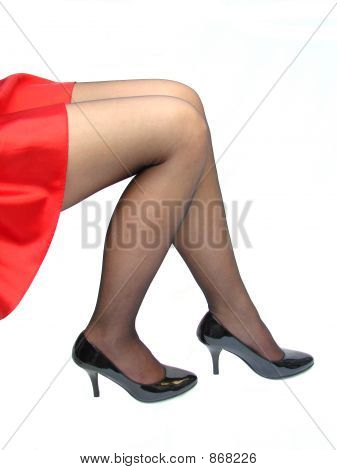 Shapely legs in sitting position with a red dress and high heels poster