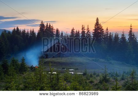 Summer evening. Mountain landscape. Camping in nature. Bonfire near the house